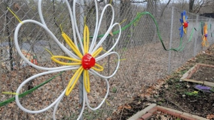 Montessori 1 Old hoses and baking pans become flowers on a fence at the Montessori Centre Academy in Shaler.