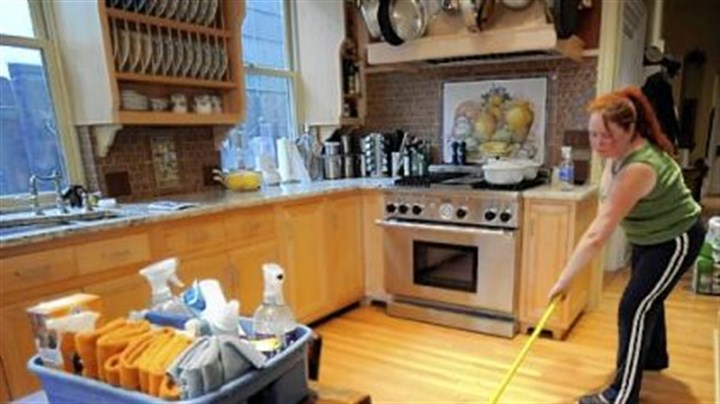 mop solution Heather Kniess of Shiny Happy Cleaners swabs the decks in a client's kitchen in the Mexican War Streets on the North Side with a diluted vinegar-and-water solution. The solution leaves no residue on the hardwood floor that can catch dirt later or discolor the wood.