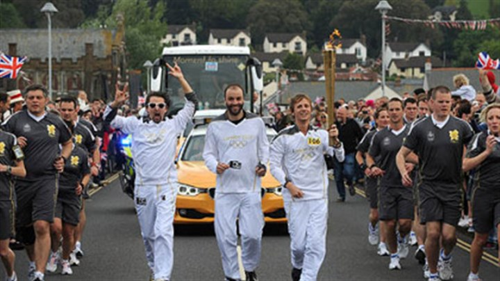 Muse carries the Flame Torchbearers Matt Bellamy, Dominic Howard and Christopher Wolstenholme, from the band Muse, carry the Olympic Flame on the leg between Torquay and Teignmouth.