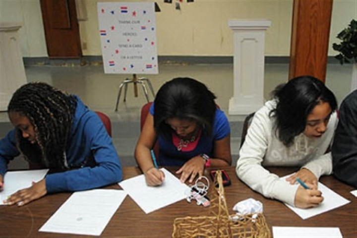 National Day of Service K'sandra Harding, 13, Jada Doleno, 13, Nila Andrews, 14, and Roman Burkes, 14, from the Melting Pot Ministries in the South Hills join in the National Day of Service in honor of Martin Luther King Jr. at the Homewood AME Zion church by writing letters to members of the military.