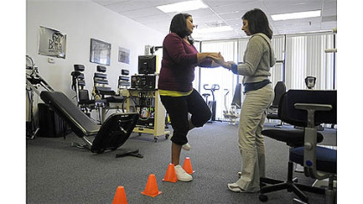 Nettie Gibson does exercise Nettie Gibson, left, who was seriously injured by a drunken driver in August 2011, does an exercise with the help of therapist Annie Ursom at East Suburban Sports Medicine in Monroeville.