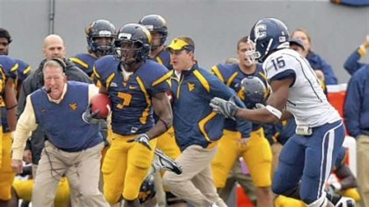 Noel Devine West Virginia's Noel Devine, center, races by head coach Bill Stewart, left, as he runs for a game-winning 56-yard touchdown in last season's game against Connecticut.