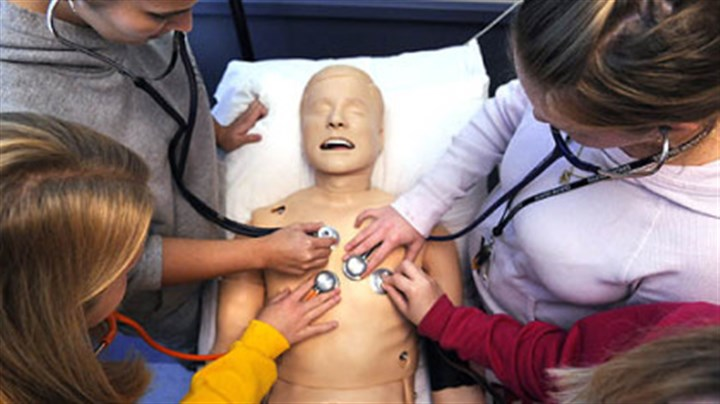 Nursing students at Carlow. Sophomore nursing students at Carlow University, clockwise from top left, Trista Corradini, Deanna Wittmer, Heidi Warner and Rachel Zajac check breathing and heart signs on a human simulator during class.