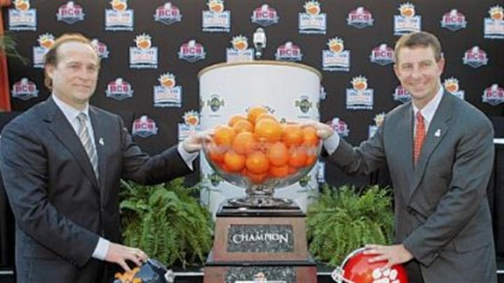 OrangeBowl West Virginia coach Dana Holgorsen and Clemson coach Dabo Swinney gather for a photo next to the trophy at a news conference Wednesday for the Orange Bowl in Hollywood, Fla.