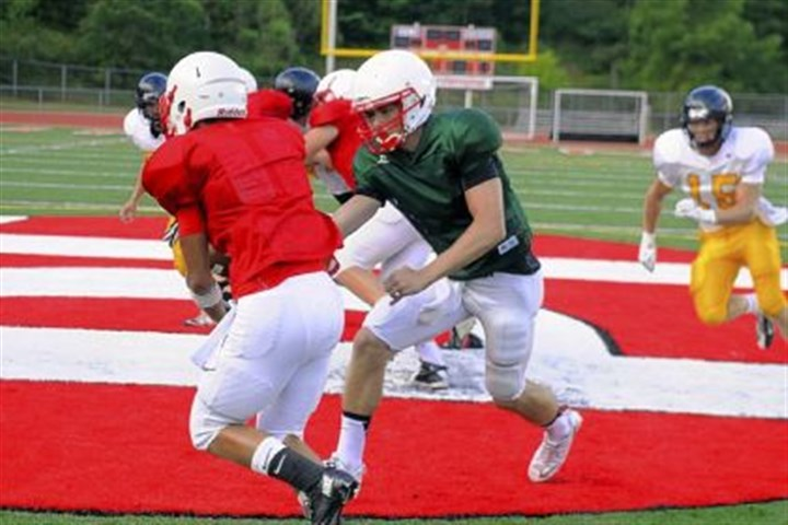 owen Peters Township quarterback Cory Owen hands off to Marcus Ubinger during a scrimmage Aug. 23.