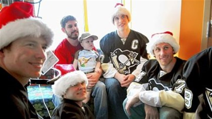 Penguins and the kids Blake Thomas and his son Michael, 2, pose for a photo with Penguins players, from left, Ruslan Fedotenko, Chris Kunitz, Sidney Crosby, and Jay McKee on Dec. 8. The Penguins players made their 26th annual team visit to patients at Children's Hospital and delivered gifts, posed for photos, and signed autographs.