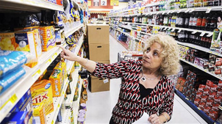 PG Photo: The coupon queen Susan Samtur checks a list of items she needs at a Shop 'n Save in Lawrenceville. Ms. Samtur has been a 'coupon queen' since the 1970s.