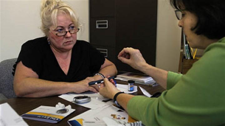 Photo Joyce Tobias of Latrobe, left, newly diagnosed with diabetes, is instructed in how to use a blood sugar testing device by Sharlene Emerson, Diabetes Educator through UPMC.