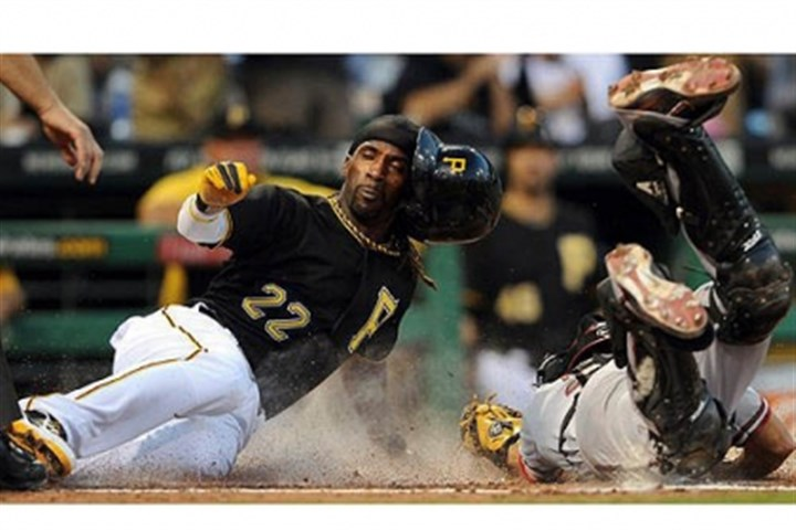 Pirates' Andrew McCutchen slides Center fielder Andrew McCutchen slides safely into home plate past Diamondbacks catcher Wil Nieves in the third inning Friday at PNC Park.