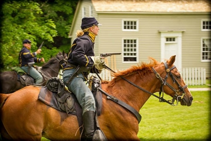 Pistol drawn Robin Shields of the 6th Ohio Cavalry charges the enemy during a mock skirmish at Hale Farm and Village in Bath, Ohio on June 1, 2013.