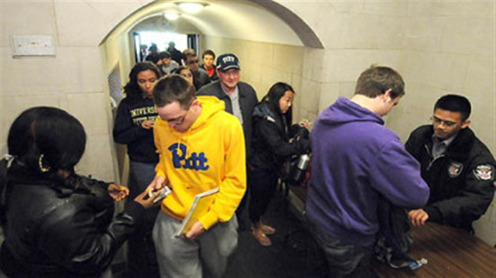 Pitt students The line snakes out the door as security officers check photo IDs and examine bags in April at the Cathedral of Learning ground floor entrance along Bigelow Blvd. Increased security procedures took effect in the wake of multiple bomb threats on campus.