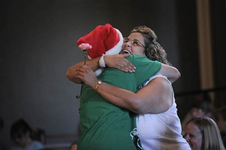 Pittsburgh Project Marion Anderson, 15, of Newport News, Va., hugs Dolores Romanelli Wednesday night after presenting her with a carnation when it was announced that volunteers at the Pittsburgh Project would fix up Ms. Romanelli's Brighton Heights' home.