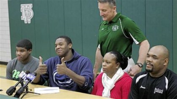 Pollard's signing Jamil Pollard gives the thumbs up after signing with Penn State Feb. 1. With him are his parents, Lucille Bevans and James Pollard, at right, Mr. Pollard's son, Brandon Holmes, left, his coach, Clyde Folsom, standing.