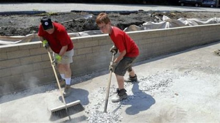Project Robert Cortese, left, helps his son, Robbie Cortese, with his Eagle Scout project, and works on putting the finishing touches on a retaining wall along the parking lot of St. Anne Roman Catholic Church in Castle Shannon.