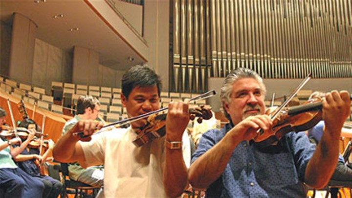 PSO in Beijing Violinst Christopher Wu (left) and concertmaster Andres Cardenes warm up with other members of the Pittsburgh Symphony at the