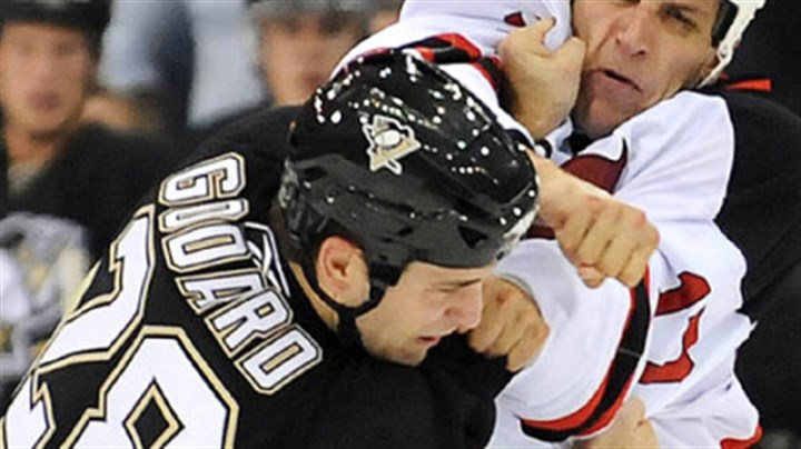 Punchie Eric Godard takes a punch from the New Jersey's Mike Rupp early in the home opener last night.
