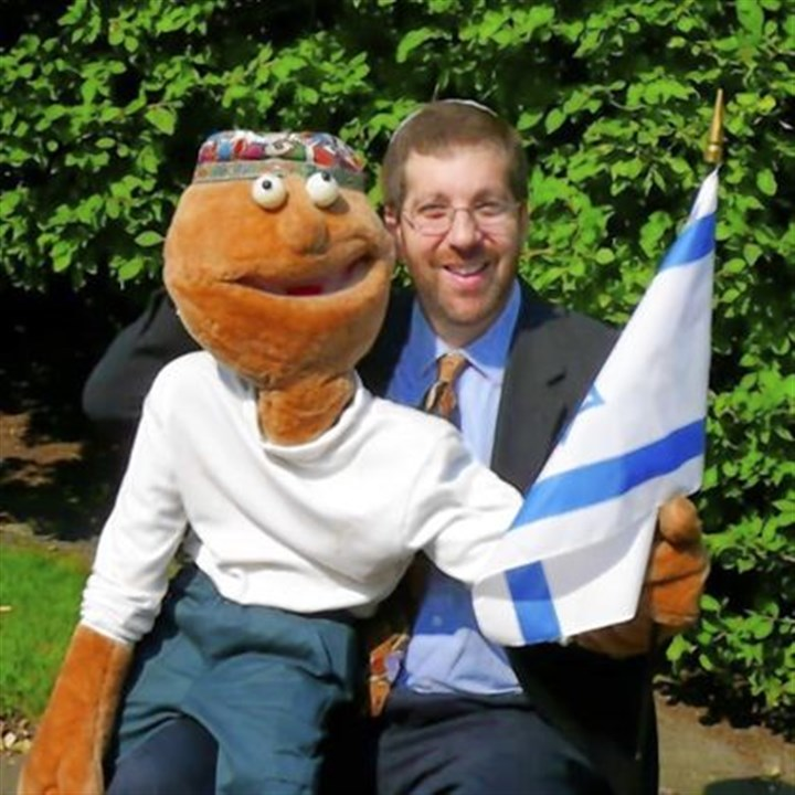Rabbi Ron Symons Rabbi Ron Symons, director of Lifelong Learning at Temple Sinai, works with a puppet named Sheli.