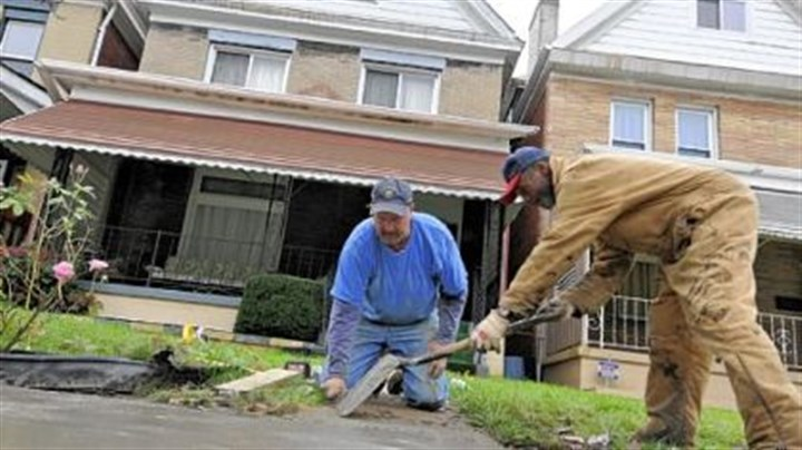 Race Street cleanup Volunteers Dave Majcher, left, and Clarence Swindle finish putting in replacement concrete outside a home in the 7400 block of Race Street in Pittsburgh's Homewood neighborhood. Volunteers and the Redd Up Pittsburgh cleanup crew took on the task of cleaning up several blocks of the street Thursday.