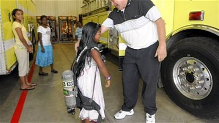 Regina Anand Regina Anand, 8, from Marshall, tries on an oxygen tank with fireman John Ashbaugh during a tour of the station. Regina donated the money she received at her first communion party to the Marshall Township Volunteer Fire Department.