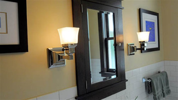 Reproduction sconces Nickel-plated sconces from Rejuvenation fit the style of the custom-made medicine cabinet.