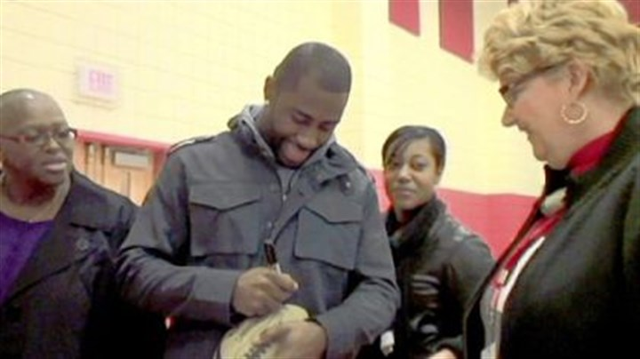 Revis reaches out Aliquippa native Darrelle Revis of the New York Jets signs a football at Aliquippa Elementary School on Monday.