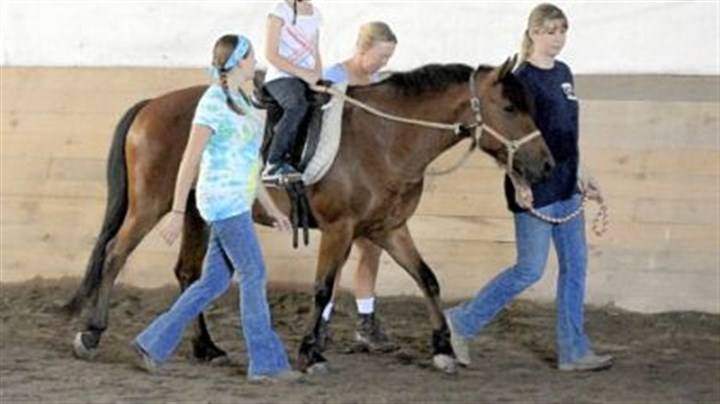 Riding along Abby Langer, 8, of Irwin rides on 6-year-old Starlight with help from Stacy Shirer, Pam Burkland and Jennifer Harbaugh at Nickers 'n Neighs.