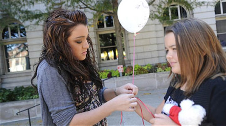 Sage and Alexa Cuccia Sage Cuccia, left, 16, of Monroeville attaches a balloon to the wrist of her sister Alexa, 10, at the National Day of Remembrance for murder victims Saturday at the Westmoreland County Courthouse in Greensburg. The girls, sisters of murder victim Demi Cuccia, were among 100 attending the memorial.