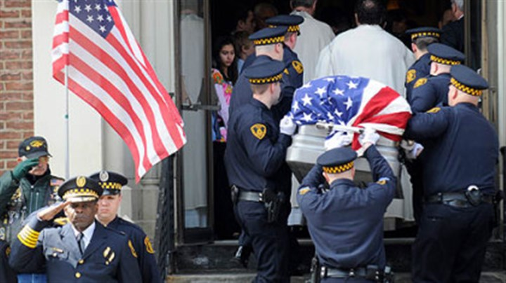 Salute Pittsburgh Police Chief Nate Harper, front left, salutes as the flag-draped casket of Officer Paul J. Sciullo II is carried into St. Joseph Church in Bloomfield for his funeral yesterday.