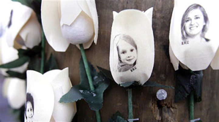 Sandy Hook Elementary School Photos showing those killed in the shootings at Sandy Hook Elementary School are imprinted on faux roses at a memorial Saturday in Newtown, Conn.