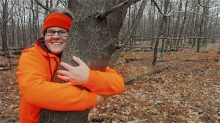 Sara Fitzsimmons hugs an American chestnut tree Sara Fitzsimmons hugs an American chestnut tree found growing in the wild near the orchard she helped plant. This tree is about 40 feet tall and is producing nuts but shows signs of chestnut blight.