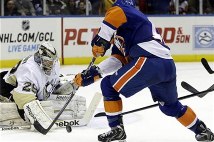 Save Penguins goalie Marc-Andre Fleury makes a save as Islanders center Keith Aucoin skates in front of the crease in the second period.