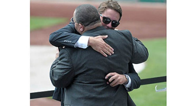 Schneider Max Schneider embraces an unidentified friend Saturday during a memorial service for his father, Mark Schneider, at PNC Park. Mark Schneider, former chairman of the Sports & Exhibition Authority and Stadium Authority, died July 29 after a bicycle accident in Maryland.