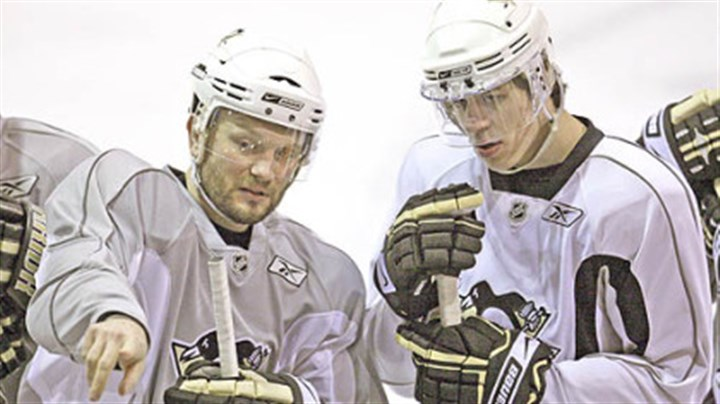 Sergei Gonchar and Evgeni Malkin Sergei Gonchar, left, explains a drill to teammate Evgeni Malkin during hockey practice at Southpointe yesterday. The Penguins take on the Carolina Hurricanes in Game 1 of the Eastern Conference finals tonight at Mellon Arena.