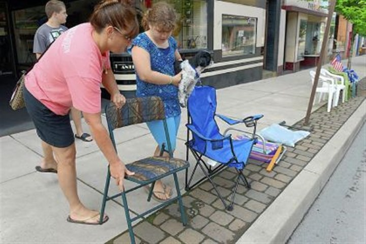 setting out parade chairs Mary Jo Marasco of Cecil sets out her family's parade chairs along Pike Street in Canonsburg with her children, Anthony, 13, and Angelina, 11, on Tuesday to save places to watch the town's Fourth of July parade. Reserving spots with chairs for the parade is a Canonsburg tradition.