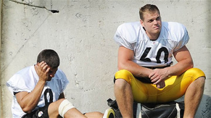 Sideline Punter Daniel Sepulveda, left, sits out the afternoon practice at Saint Vincent College yesterday.