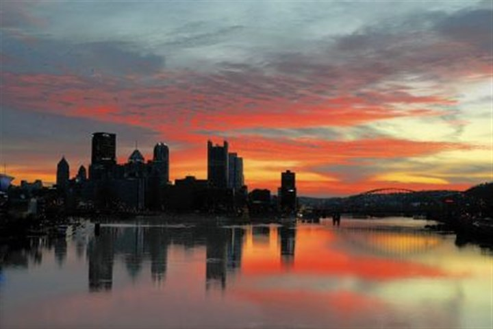 skyline for 30 Clouds turn red over the Pittsburgh skyline, reflected in the Ohio River just before sunrise.