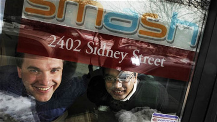 SMASH Eric Boduch, left, and Chanakya Damarla, co-founders of Smash, look through their front office door on the South Side. Smash deals with text messaging on the phone in business.