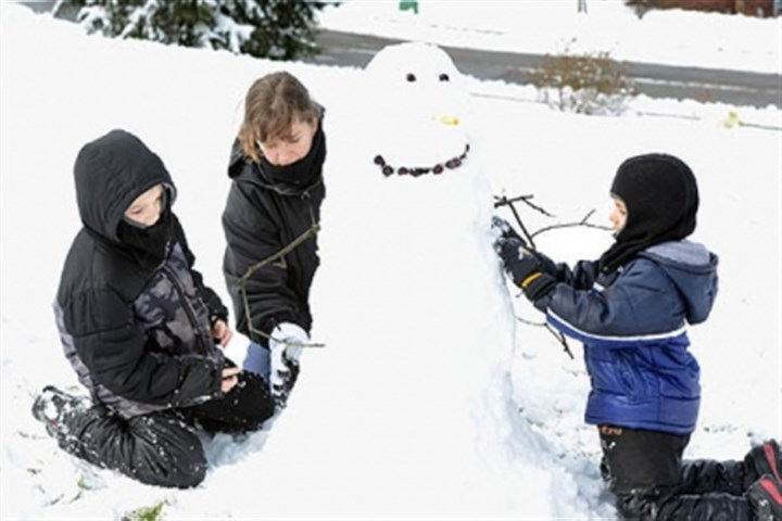 snowman in franklin park Tiffany Grimes of Franklin Park, makes a snowman with her sons, Luke, left, 8, and Hunter, 5, in their front yard today.
