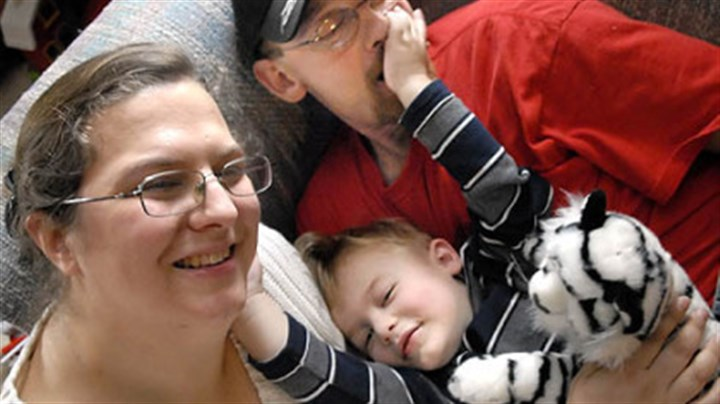 Snuggling Lori and Randy Wilson snuggle with their 2-year-old son T.J. at their Adams home on Tuesday. The boy had a heart transplant on July 16.