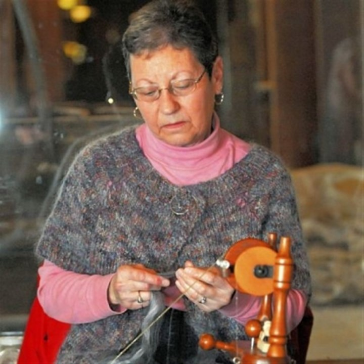 Spin 2 Lorraine Heasley from Hempfield, wearing her handmade sweater, spins yarn for another project.