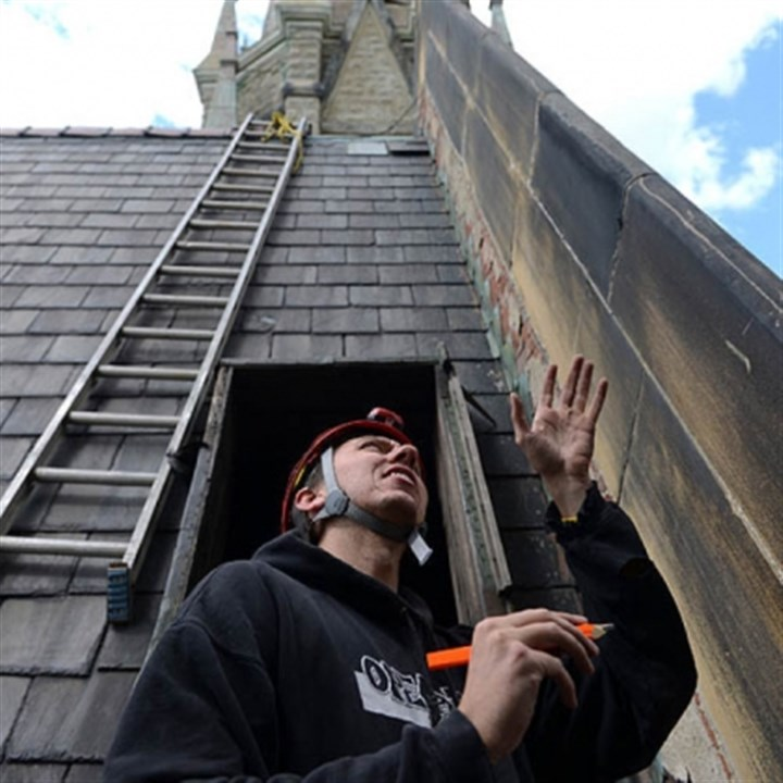 SS Peter and Paul Catholic Church on Saturday Nathan Menge of Wilkinsburg takes lumber measurements from John Zolko [not shown] who is doing roof repairs to SS Peter and Paul Catholic Church on Saturday. Both men are part of the Explorers Club and used climbing gear to access sections of the steeple and roof.
