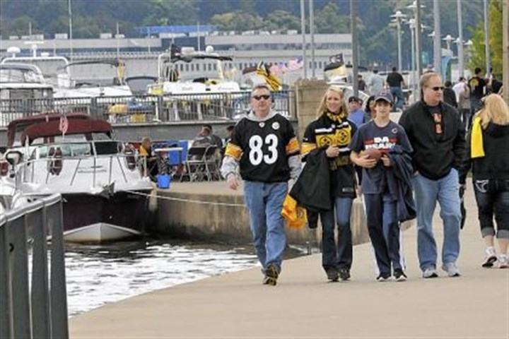 Steeler fans Returning Pittsburghers Jim Ross, left, and his daughter Emily, second left, now of Greenville, S.C., enjoy the Riverwalk on the North Shore on Sunday before the Steelers game. They came in with their neighbors, Chicago Bears fans Andrew Wetzel, 14, and his father Paul Wetzel, right. They said that they had no trouble parking or using the T to get to the North Shore.