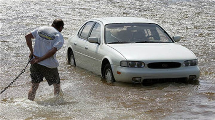 Storm surge A concerned neighbor helps tow a car as a storm surge from Hurricane Isaac pushes into Panama City, Fla.