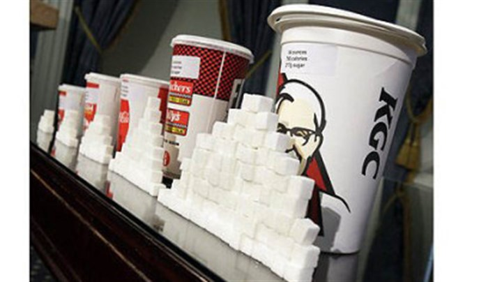 Sugar Cubes Various size cups and sugar cubes are displayed at a news conference at New York's City Hall Thursday. New York Mayor Michael Bloomberg is proposing a ban on the sale of large sodas and other sugary drinks in the city.