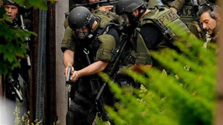 Surrounded Pittsburgh's SWAT team converge on a man who was critically wounded by police during a standoff in Larimer.