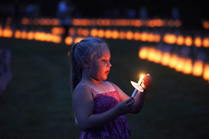 Taylor Lawrence Taylor Lawrence, 5, of Mechanicsburg, Cumberland County, holds a candle during a vigil Sunday at Soldiers' National Cemetery at Gettysburg. Luminaria mark each of the more than 3,500 graves of soldiers killed in 1863 in the Battle of Gettysburg.