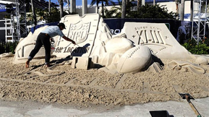 Team Sandtastic Mark Mason of Team Sandtastic puts the finishing touches on a sand sculpture at the NFL On Location Beach House outside the entrance to Raymond James Stadium yesterday in Tampa, Fla.