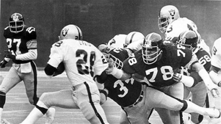 Team work Andy Russell (34), Dwight White (78) and Jack Lambert (58) collar Clarence Davis after a 7 yard gain in this 1976 photo.