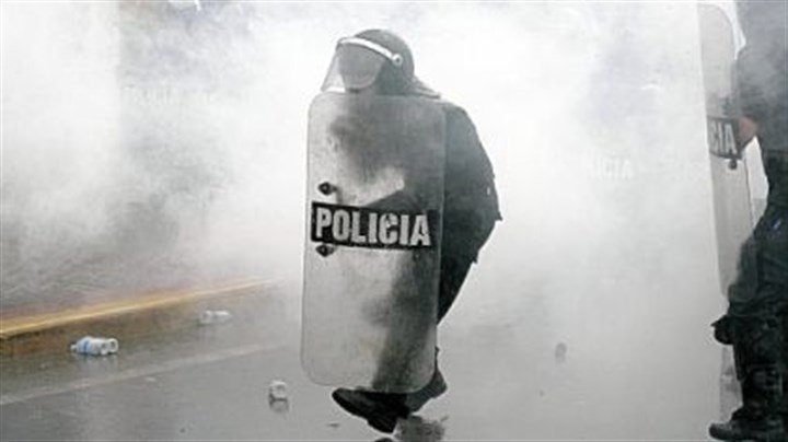Tear gas Surrounded by tear gas, police officers move forward during a protest against Venezuelan President Hugo Chavez in Caracas.
