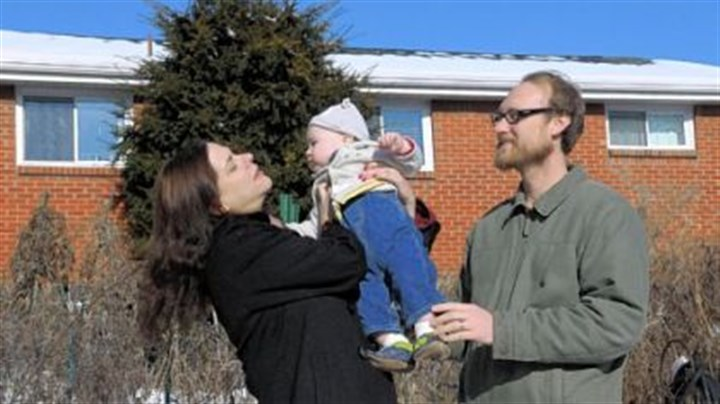 The flap Heather Fowler and Aaron McGregor hold their son, Emmett McGregor, 12 months, in the backyard of their home.